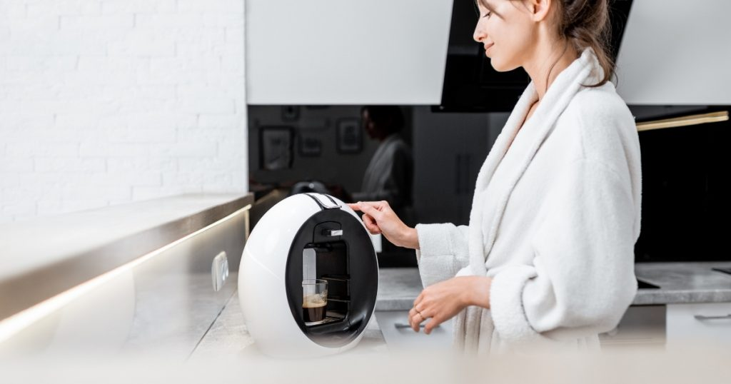 an image of a girl using the best coffee pod machine