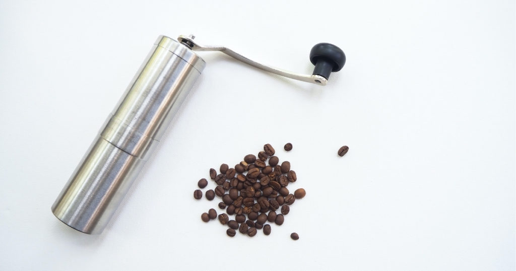 an image of the best manual grinder with some coffee beans